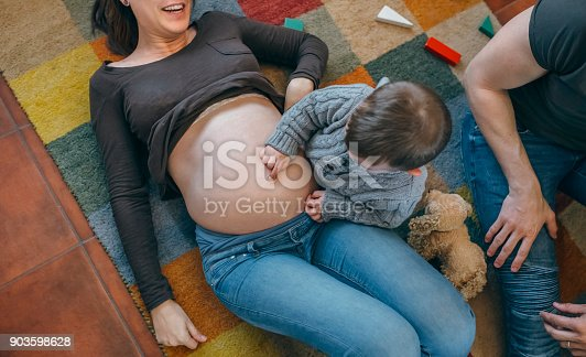istock Toddler tickling the belly of his pregnant mother 903598628