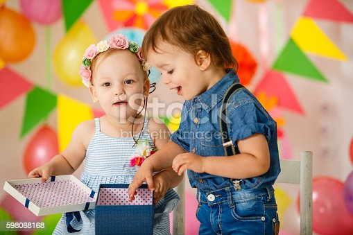 istock Toddler twins opening present at birthday party 598068168