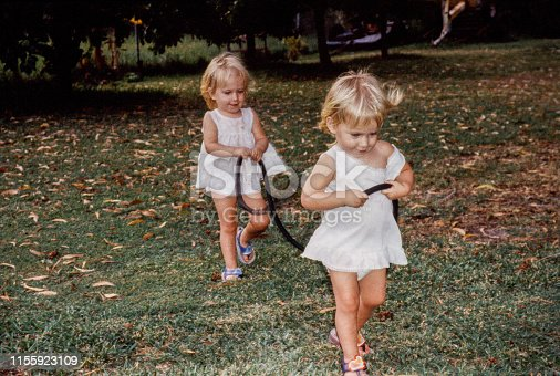 Two female twin sisters are playing outdoors. They are playing with a long rope like horses. Its a summer day for this horizontal image with fill flash.