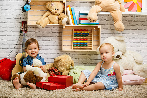Toddler twins playing together at home stock photo