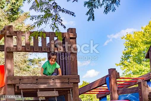A little boy, about 2 years old, looks down from the high platform on a wooden play structure. Enjoying the playground, the toddler wears a green shirt as he plays.