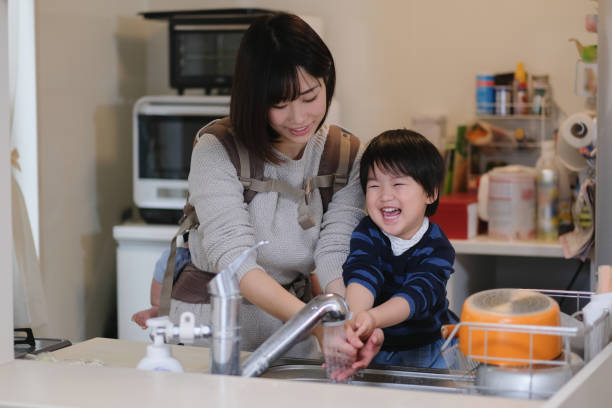Toddler washing hands with mother at kitchen Everyday life of child in house homemaker stock pictures, royalty-free photos & images