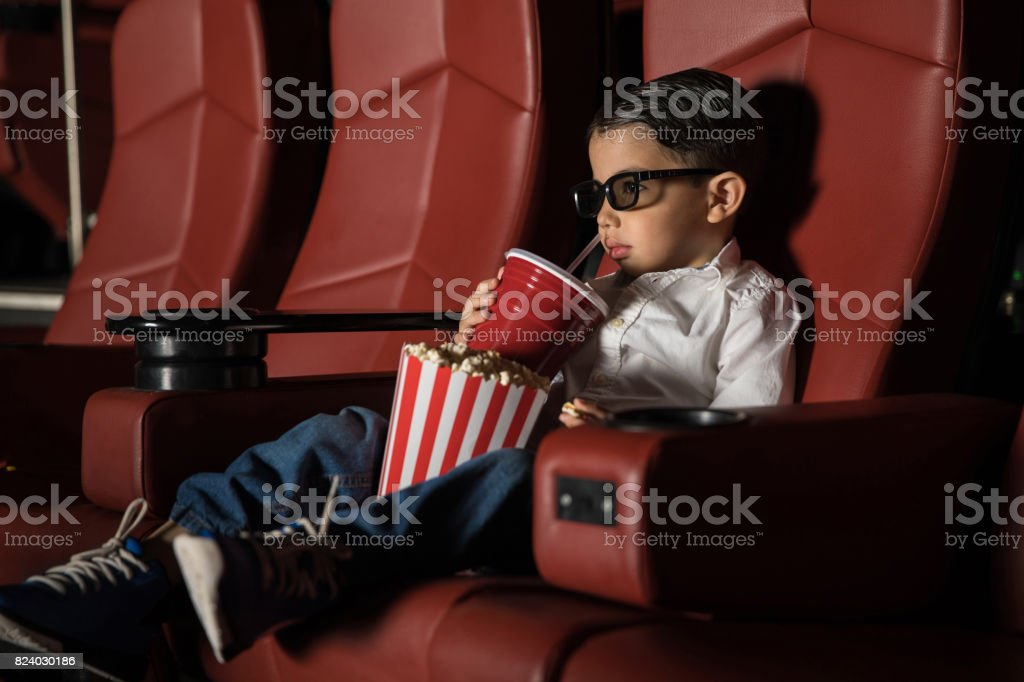 Toddler watching movie at a cinema theater stock photo