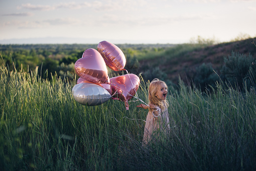 3 year old toddler girl in a pink dress holding heart-shaped ballons outdoors in tall green grass.