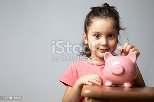 Toddler wearing pink t-shirt is putting coins into her piggy bank in front of a blank gray wall.