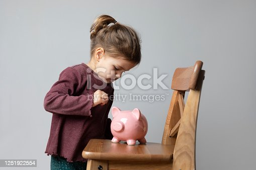 Toddler with is putting coins into her piggy bank in front of a blank gray wall.