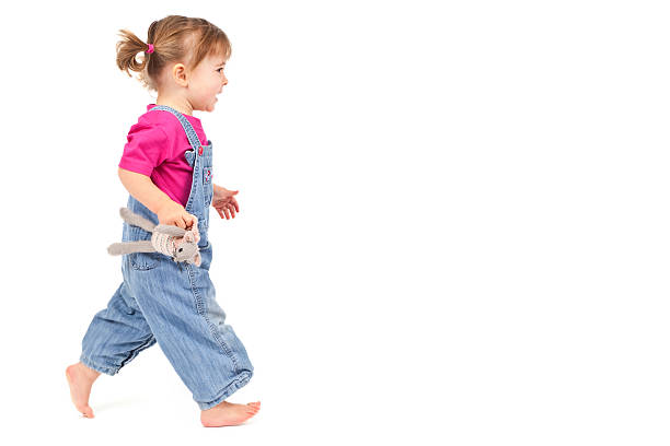 Toddler with pigtails  running across white stock photo
