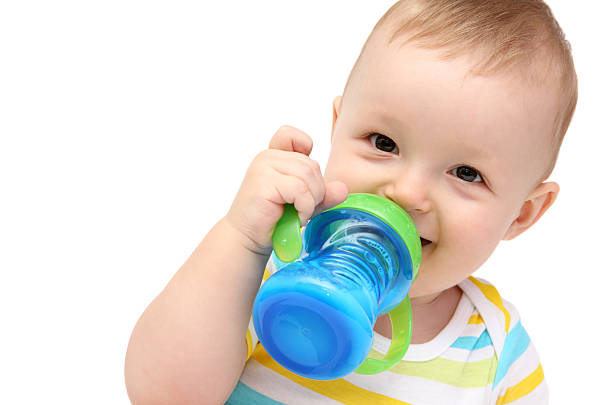 Toddler with sippy cup and milk stock photo