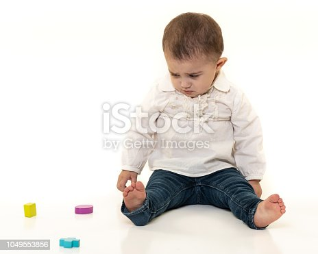 667590810 istock photo Toddler with Wooden Shape Toys 1049553856