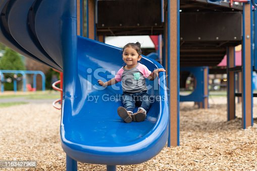 A cute young Native American girl comes to the bottom of a slide on the playground. She has a big smile for the camera.