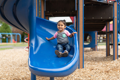 A toddler-age girl riding down the slide
