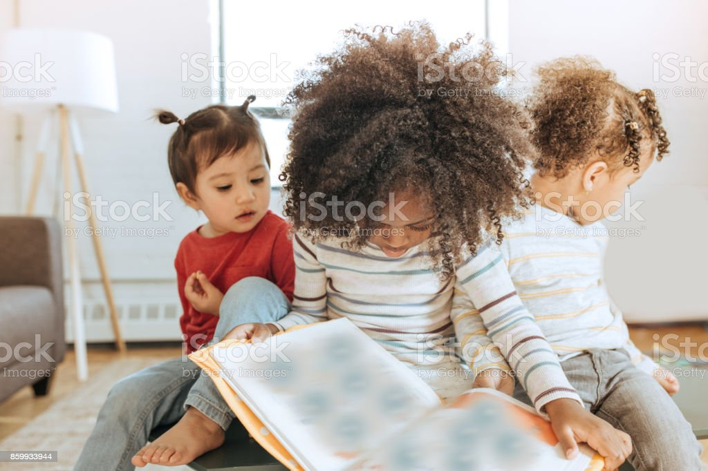 Toddlers and a book stock photo