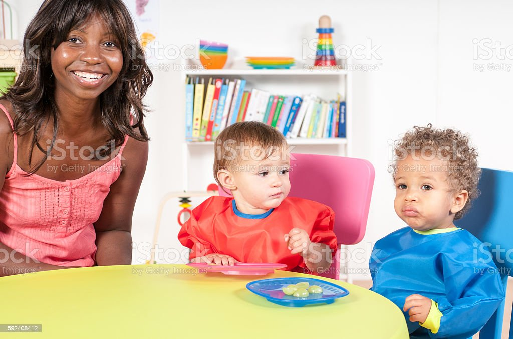 Toddlers Eating in the Nursery stock photo