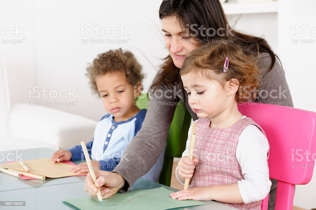 Toddlers Enjoying Artwork In The Living/ Play Room With Carer royalty-free stock photo