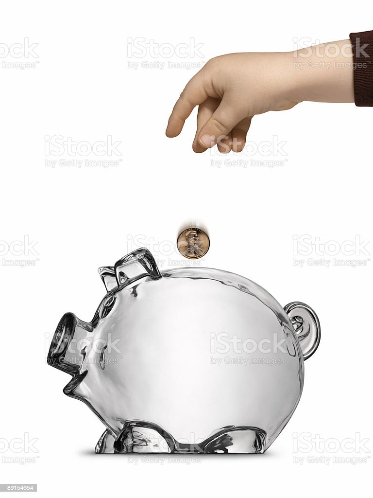 Toddler's Hand Dropping Coin into Clear Empty Piggy Bank Isolated royalty-free stock photo