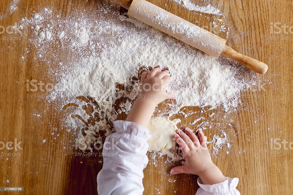 Toddler's hands playing with white flour and rolling pin stock photo
