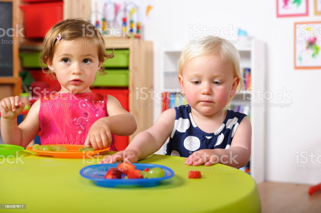 Toddlers Having Healthy Snacks In A Nursery royalty-free stock photo