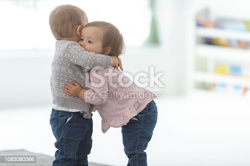 Two toddlers are standing in a playroom and hugging each other.