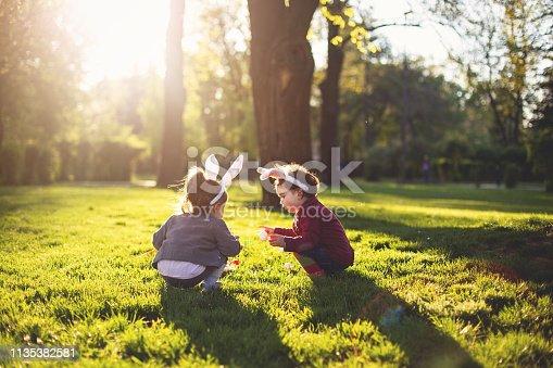Cute little toddler sister enjoying the easter egg hunt in the park.