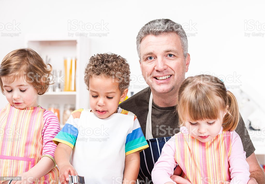 Toddlers/ Little Children Being Supervised By Carer/ Father stock photo