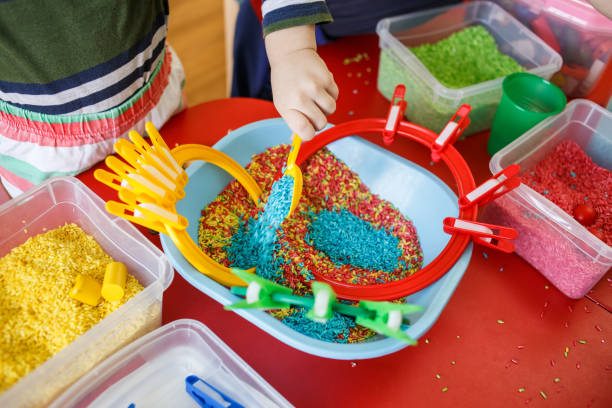 Toddlers playing with sensory bin with colourful rice on red table stock photo