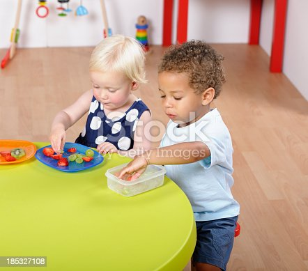 Toddlers/ pre-schoolers having a healthy snack in a nursery setting.