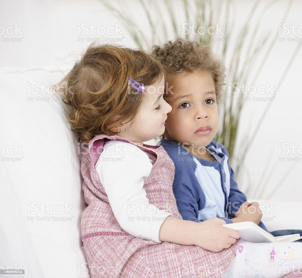 Toddlers Reading Book On The Couch/ Sofa stock photo