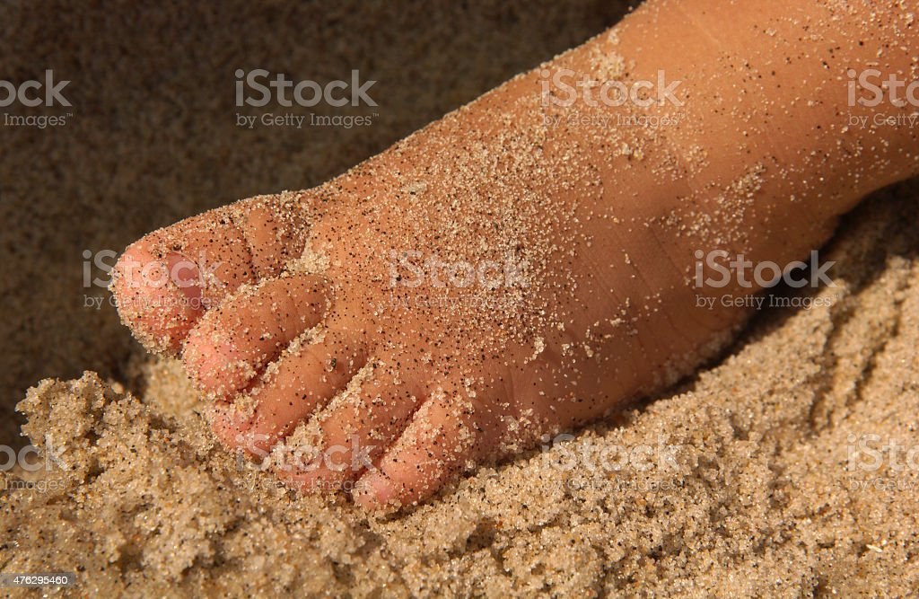 Toddler's Sandy Foot on Beach at Seashore stock photo