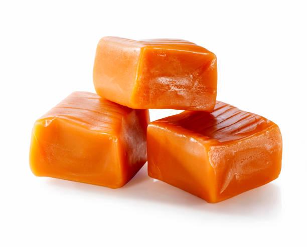 toffee karamel snoep close-up geïsoleerd op witte achtergrond - kauwgomachtig stockfoto's en -beelden