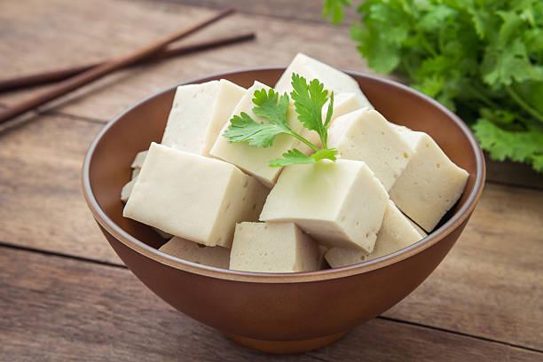 tofu cubes in bowl and parsley - tofoe stockfoto's en -beelden