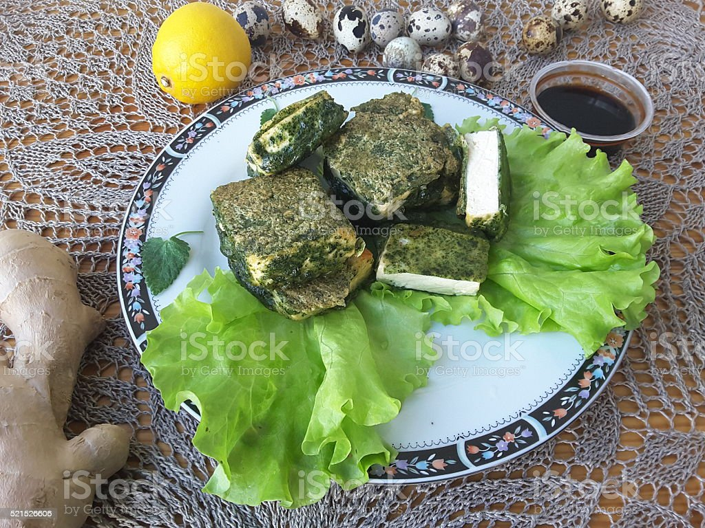 Tofu in green nettles tempura, on plate with lettuce stock photo