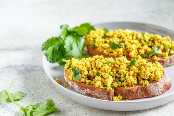 tofu scramble sandwich op een grijze plaat. vegan food concept. - vleesvervanger stockfoto's en -beelden