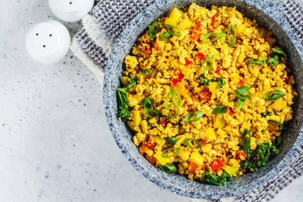 tofu scramble met groenten in een pan. veganistisch alternatief omelet. - vleesvervanger stockfoto's en -beelden