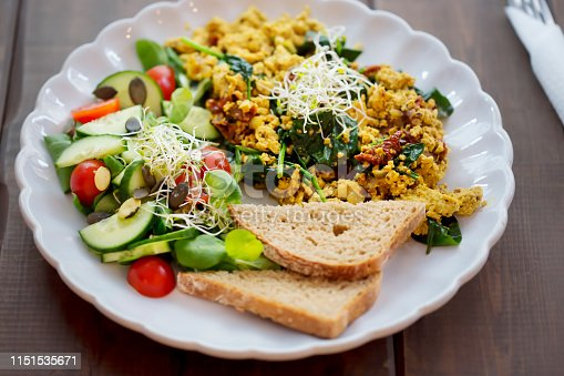 Tofu scrambled eggs with sun dried tomatoes & spinach and tomato & cucumber salad, with bread