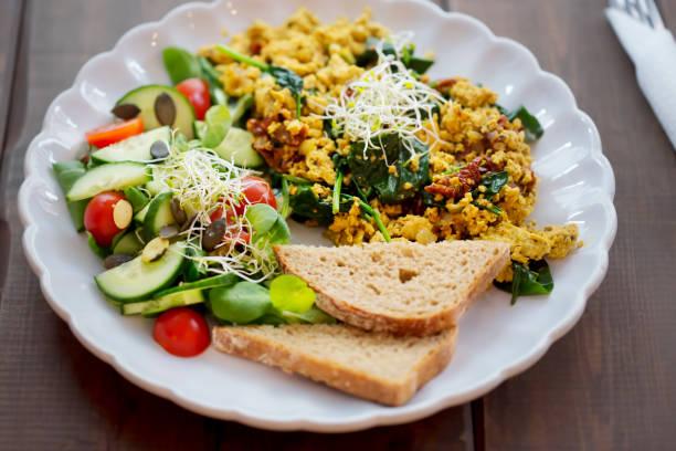 tofu roerei met zongedroogde tomaten & spinazie en tomaat & komkommer salade, met brood - tofoe stockfoto's en -beelden