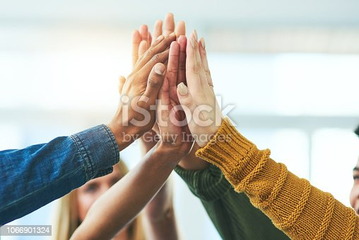Closeup shot of a diverse group of people high fiving together