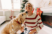 Photo of young woman and her dog enjoying together at home in a Christmas atmosphere