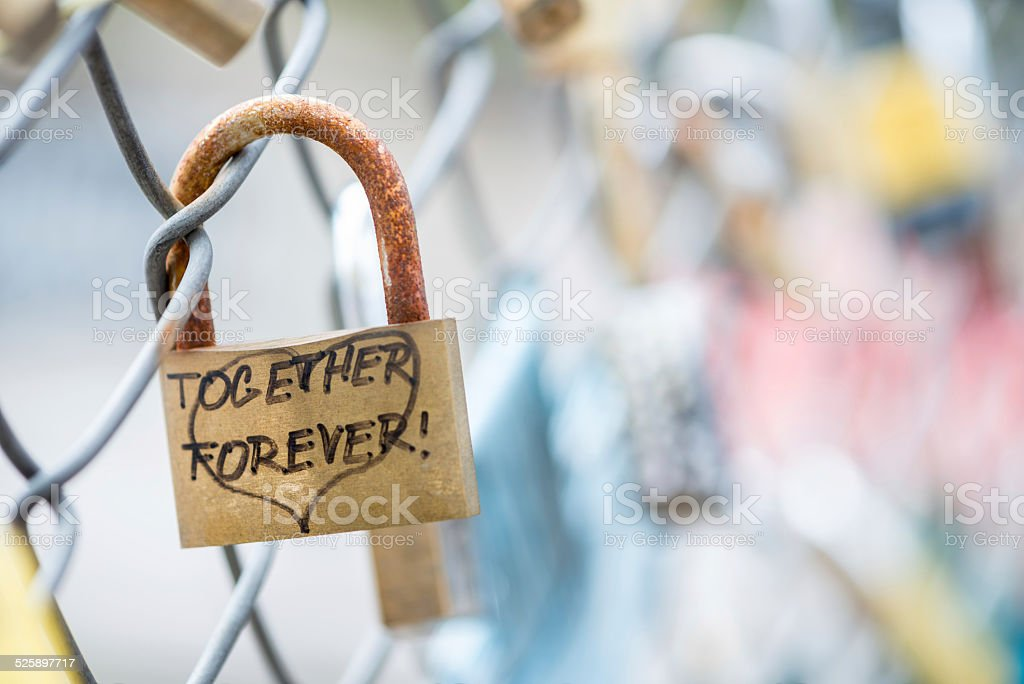 Together Forever Handwritten on Rusty Padlock Locked to Fence stock photo