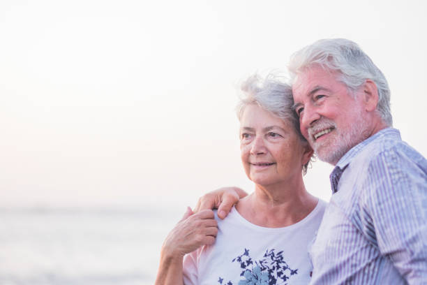 Together forever life and new horizon for a retired couple happy in outdoor hugging and loving  happy old prople holding hands and enjoy - white bright clear sky background for senior portrait stock photo