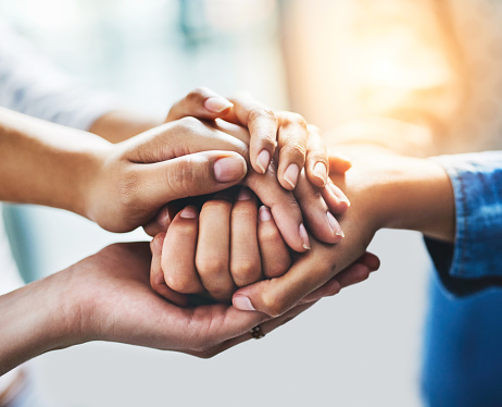 Closeup shot of a group of unrecognizable people joining their hands together in a huddle