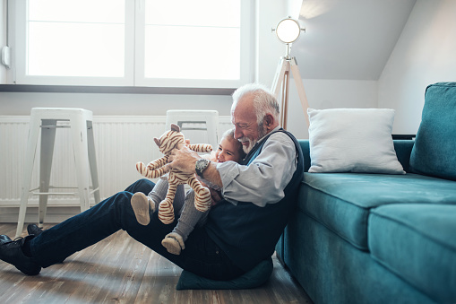 Mature man playing with granddaughter at home.