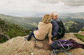 Photo of an elderly couple during their hike with backpacks, reached the top of the mountain