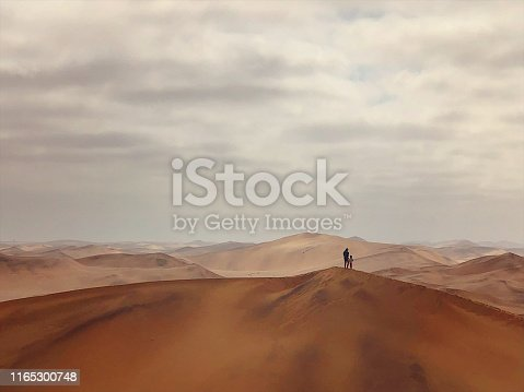 Two girls, one a toddler, standing on top of a sand dune after hiking top the top of Dune 7 at Walvis Bay Swakopmund with a cloud backdrop copy space Namibia Africa