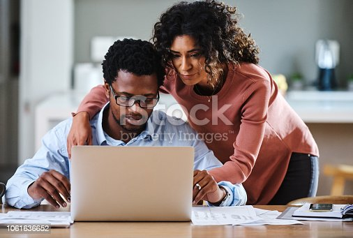 Cropped shot of a young married couple working on their financial budget together in the kitchen at home