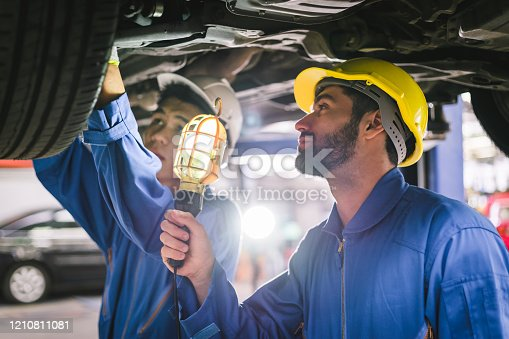 136591855 istock photo Together we can! : Team mechanics concepts - checking and repairing the car in the workshop garage 1210811081