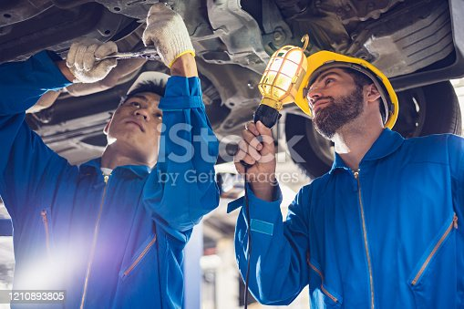 136591855 istock photo Together we can! : Team mechanics concepts - checking and repairing the car in the workshop garage 1210893805