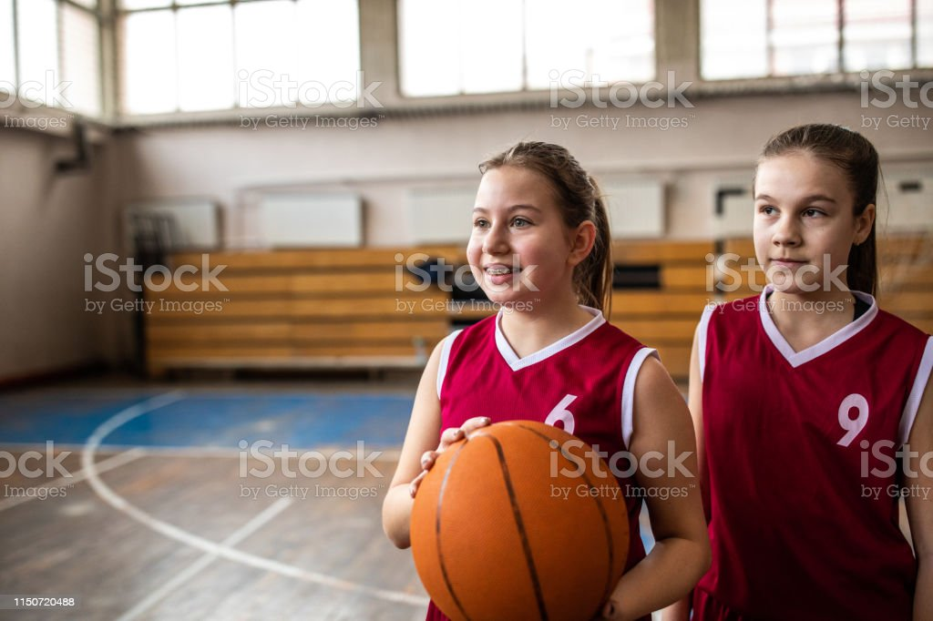 Satisfied teenage girls standing and holding basketball ball after...
