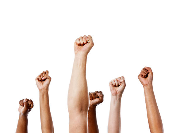 together we stand! many clenched fists punch air energetically - fist stock photos and pictures