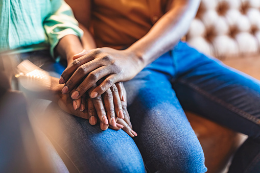 Closeup shot of an unrecognizable couple holding hands while sitting on sofa during the day.