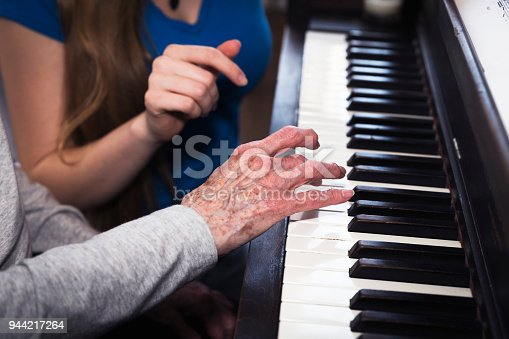 Close up of the hands of a granddaughter and grandmother working together to learn the piano.